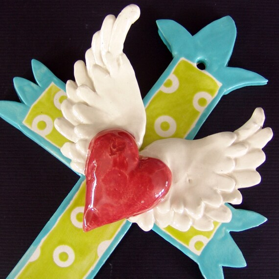turquoise cross with large winged heart