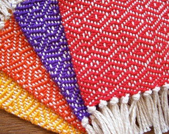 handwoven coaster set in red orange yellow and purple