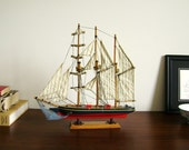 Vintage model sailboat, wood base ship, white, red with linen sails