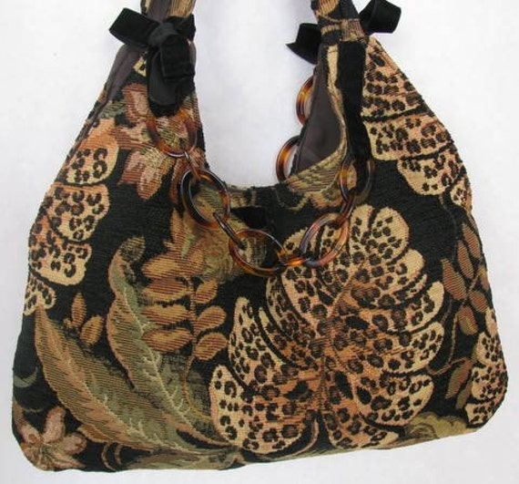 slouchy hobo shoulder bag with faux tortise chain accent in a bold leafy floral print fabric