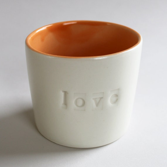 love cup, a tangerine orange on the inside, sugary ivory outside