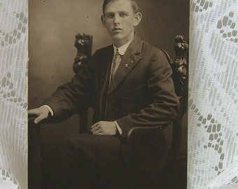 Vintage Sepia Toned Photograph of a Young Man in an Ornate Chair with a Flag Pin and a Cross Pin