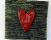 Red ceramic heart wall tile with Sandy green texture background