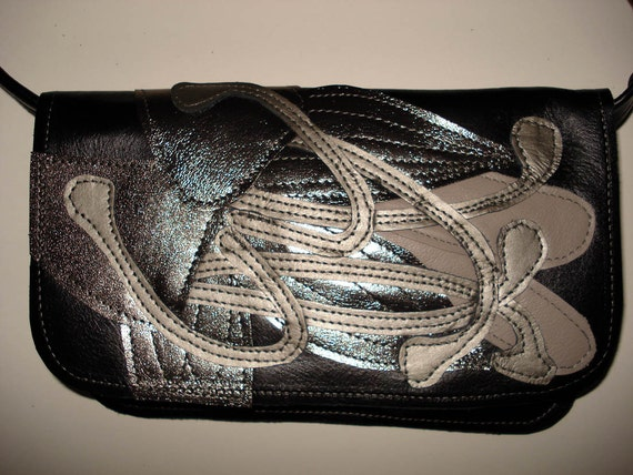 Shoulder strap Clutch bag in Black leather with metallic anthracite applique Lily