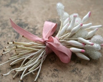 elongated cream stamens with pink tips wrapped in silk ribbon
