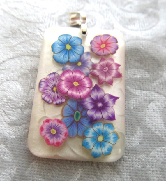 multi colored flower polymer clay cane slices in resin pendant