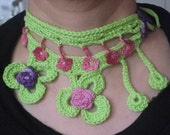 A freeform necklace in light green with pink and purple flowers