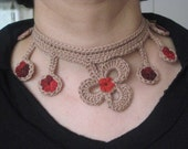A freeform necklace in beige with red-bourdeaux  flowers