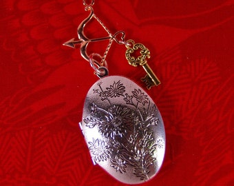 Elongated Floral Decorated Silver-tone Locket with Archery and Key Charms