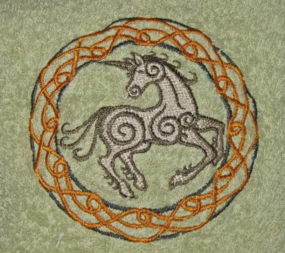 Crochet Hanging Celtic Unicorn on a green towel with a dark green top