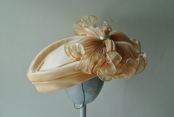 Luxurious vintage 80s  pastel  peach color , oval shape pillbox hat with a large bow.  Made by Chapeau Creations