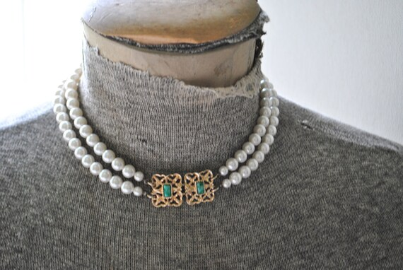 Vintage 70s two strand white pearl choker necklace with gold tone metal filigree bar and teal stone. Made by Sarah Coventry.