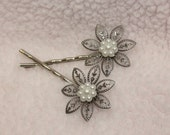 Pair of silver bobby pins with flower center