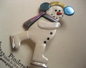 Skating snowman pin with chartreuse blue earmuffs and irridescent green scarf brooch