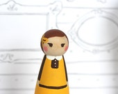 Jane the wood doll is yellow and chocolate