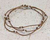 triple wrap bracelet or necklace. light brown cotton cord. sterling silver beads.