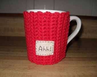 crocheted coffee mug cozy or tea mug cozy in red with hand embroidered tag that says Ahh eco friendly