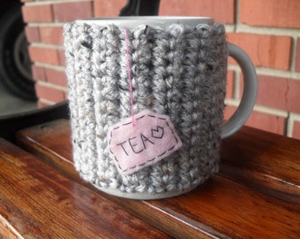 Crocheted mug cozy in gray grey marble with hanging pink tea bag