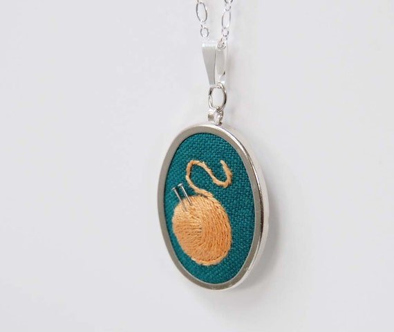 Embroidered Necklace Knitting Pendant Necklace Orange Yarn on Teal Green Linen in Pendant Setting