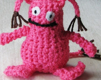 Crocheted monster in hot pink with brown tassels and googly eyes, 4.5 inch tall