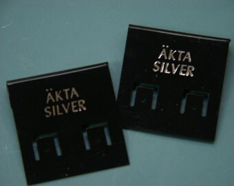Lot of 100 small unused black plastic earring holder card marked ÄKTA SILVER in Swedish (echtes silver) tabbed for standard displays.