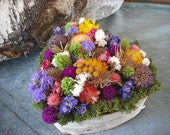 Handmade colorful dried flowers centerpiece in birch bark covered heart vase.
