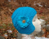 Teal blue cap with ear flaps and flower brooch.