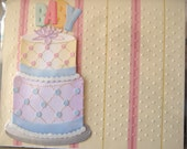 """Baby card, embossed pink and yellow paper with cake embellishment that says """"Baby"""""""