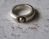Silver ring with a gold drop.