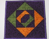 Purple, green and gold fabric coaster