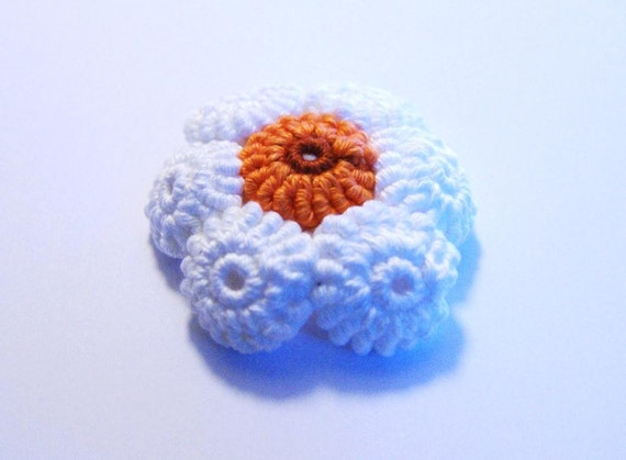 3D crocheted white flower with orange middle
