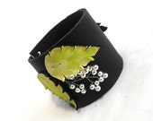 Leather bracelet with fresh green leaves