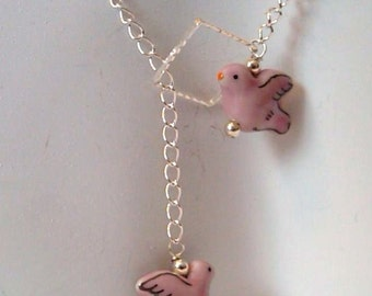 19 inch lariat s/p curb chain with 2 pink hand painted porcelain birds wired with sterling silver