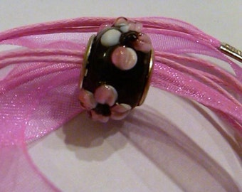 CLOSEOUT Black bead glass lampwork with pink and white flowers on a pink ribbon necklace cord