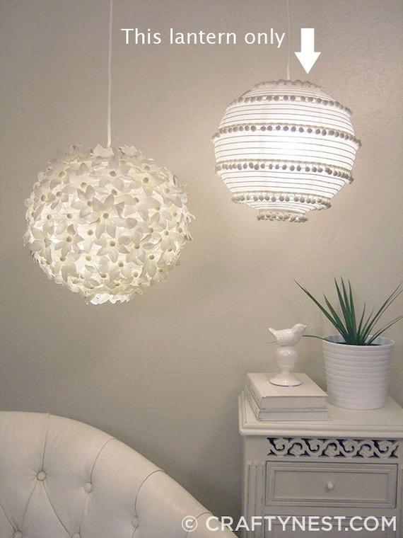 White paper lantern with pom-poms