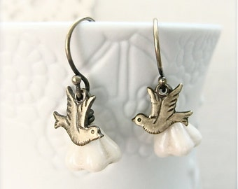 Dainty antique brass bird earrings with creamy white glass flowers.