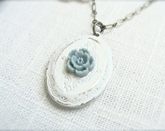 Weathered vintage style locket necklace with a small blue flower. Antique white photo keepsake gift. Jewelry by Sweet And Simple.