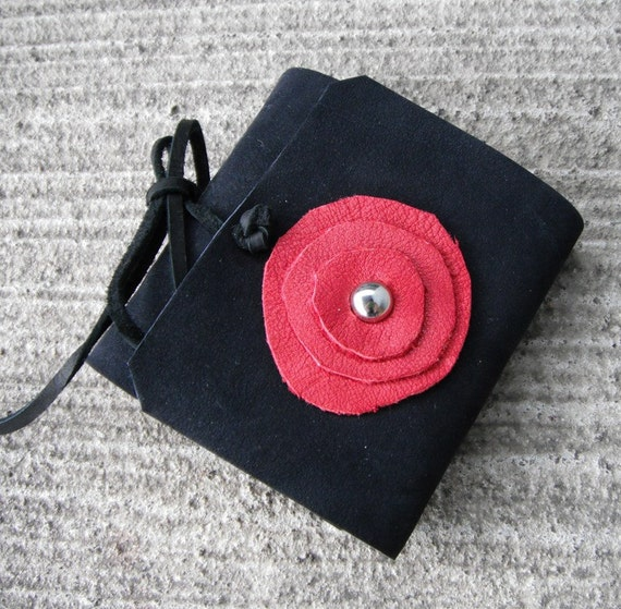 Black mini book with red leather flower.