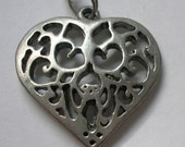Silver heart pendant with cut out swirls