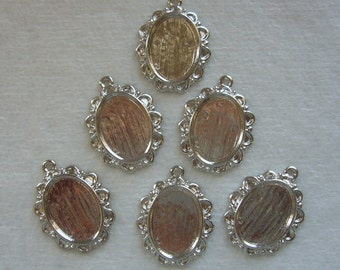 12 silver tone pendants with 18x13 glue in settings