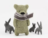 A olive green bear with grey scarf brooch