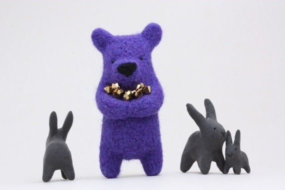 A violety blue bear with golden crystals in paw, brooch