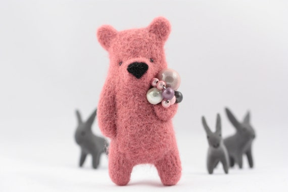 A pink bear brooch with pearls in paw
