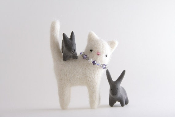 White cat with a light blue necklace, brooch