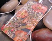 Summer apricot, tangerine, peach, colored flowers behind rectangle 1x2 inch glass. Real flowers pressed