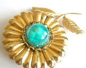 Vintage gold tone flower brooch with teal cab center