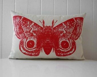 Giant Io Moth silk screened cotton canvas throw pillow 12x18 inch red on sandstone