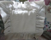 A vintage white embrodiered cottage chic pillow with white linen ruffle.