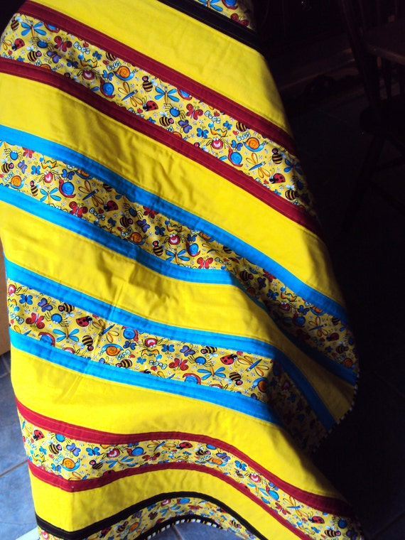 Baby or toddler quilt in bright yellow, blue, red & black featuring an adorable bug print