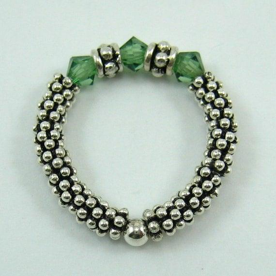1 sterling silver stretch ring with erinite green swarovski